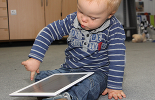 "Photo: small child with Down syndrome ""wipes"" on iPad."