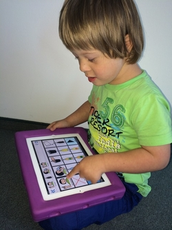 Photo: young boy with special needs uses an iPad