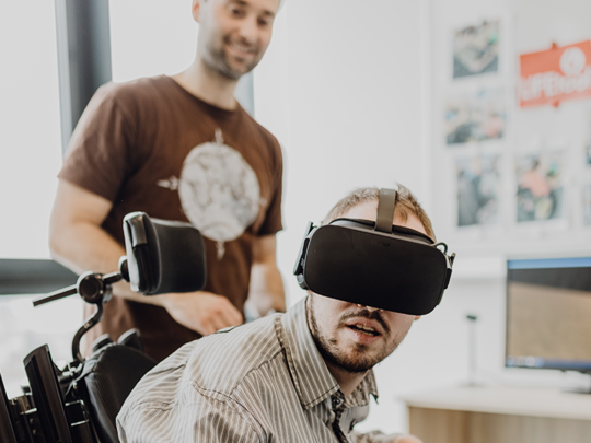 Photo: young man in wheel chair with VR glasses, LIFEtool coworker in backgrounde