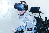 Photo: young man in a wheel chair using Virtual Reality