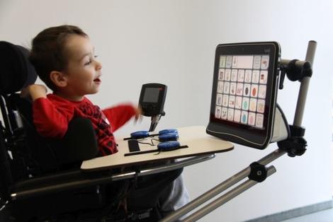 Foto: Kind im Rollstuhl mit einem Augensteuerungscomputer