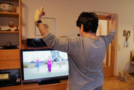 Photo: Senior citizen is exercising in front of television
