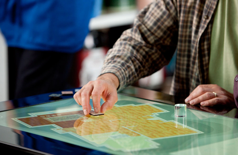 Foto: Ein älterer Mensch bedient einen Microsoft PixelSense Tisch