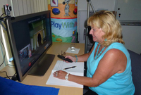 Photo: A Woman is testing HOMEdotOLD program on her TV-set