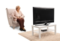 Photo: Laughing elderly lady in front of the TV set; LIFEtool research project MEK, Shutterstock photo