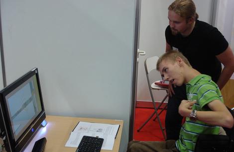 Foto: Junger Mann im Rollstuhl steuert PC mit Microsoft Kinect