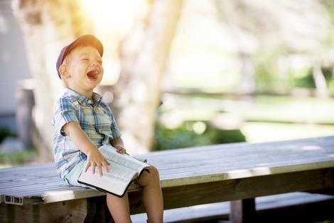 Foto: Lachendes Kind, das in einem Buch blättert, Fit4Speech, LIFEtool