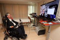 Photo: A man in a wheel chair - Prof. Sang-Mook Lee - communicates with the IntegraMouse Plus - a mouth controlled device by LIFEool