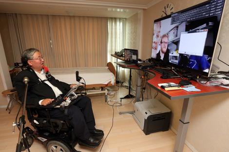 Foto: Ein Mann im Rollstuhl - Prof. Sang-Mook Lee - kommuniziert mittels mundgesteuerter Computermaus - der IntegraMouse Plus von LIFEtool.