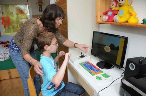 Projektbild aus SENNET: Eine Lehrerin zeigt einem Schüler auf dem Bildschirm eine Aufgabe
