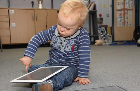 Foto: Kleines Kind bedient ein IPad