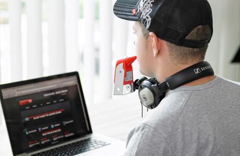 Foto: Junger Mann im Rollstuhl bedient Computer mit der IntegraMouse Plus
